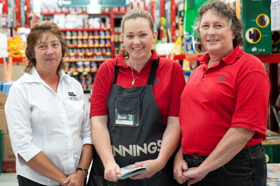 OCTEC consultant, client and Bunnings staff member standing in Bunnings smiling at the camera