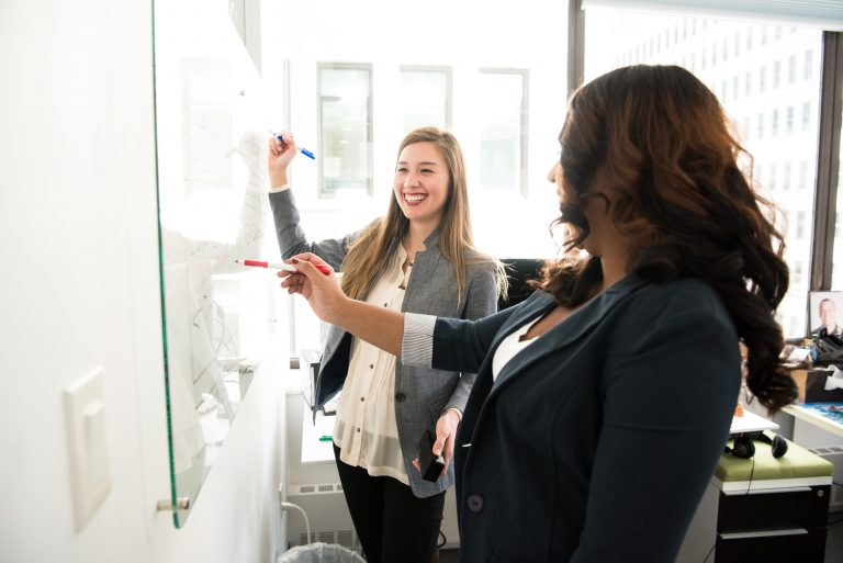 Two women writing on board in office