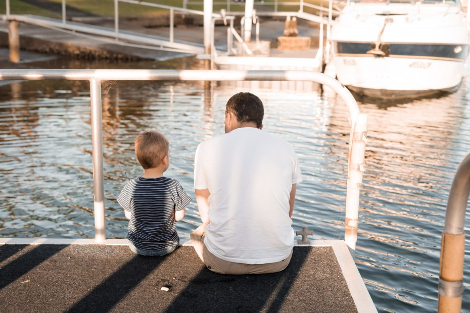 Father and Son sitting on pier looking at the water